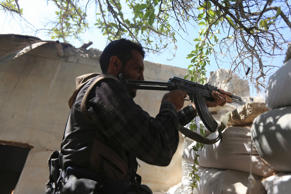 A fighter from the Free Syrian Army's Al Rahman legion fires his weapon on the frontline against the forces of Syria's President Bashar al-Assad in Jobar, a suburb of Damascus, Syria July 27, 2015.