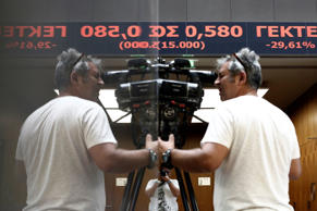 Members of the media film the stock price ticker screen following the reopening of the Athens Stock Exchange in Athens, Greece, on Monday, Aug. 3, 2015