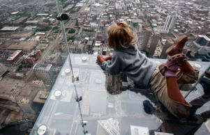 "Anna Kane, 5, looks down from ""The Ledge,"" at Chicago's 110 story, 1,450 foot Willis Tower."