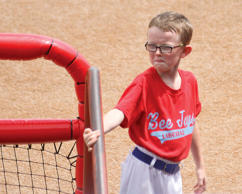 In this Aug. 1, 2015, photo, bat boy Kaiser Carlile, 9, gets ready for a National Baseball Congress World Series baseball game between the Liberal Bee Jays and San?Diego Waves outside the dugout in Wichita, Kan. Kaiser, who was wearing a helmet, was accidentally hit in the head during the game by a follow-through swing near the on-deck circle. He died on Sunday.