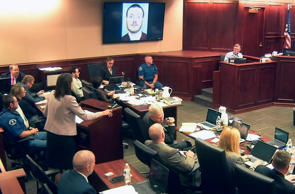 In this image made from Colorado Judicial Department video, defense attorney Tamara Brady, standing, questions Robert Holmes, top right, the father of James Holmes, background center, during the sentencing phase of the Colorado theater shooting trial in Centennial, Colo., on Tuesday, July 28, 2015. A photo showing James Holmes is displayed on a monitor. Colorado Judicial Department/AP