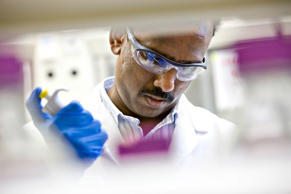 A senior scientist works on protein sciences in a lab.
