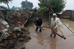Mean clear up next to a partially damaged house in a flooded area in Nowshera district, in the Khyber Pakhtunkhwa province of Pakistan on August 3, 2015.