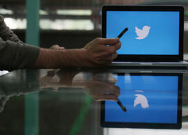 An Apple Inc. iPhone 6 smartphone is held as a laptop screen shows the Twitter Inc. logo in this arranged photograph taken in London, U.K., on Friday, May, 15, 2015.