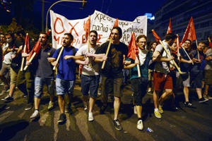 Protesters march holding banners and flags in front of the Greek parliament in Athens during an anti-austerity protest on July 15.