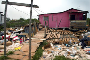 A house is surrounded by overflow from a sewage collection pond in Belize City in April, 2005.