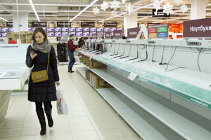 A woman walks past the empty shelves in an electronics shop in Minsk in December, 2014. Belarusians had snapped up electronics before prices began to soar.