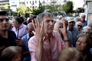A man gestures as pensioners line outside a national bank branch to withdraw cash in Athens in July.