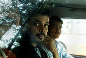 Indian test cricketer Shantakumaran Sreesanth, foreground, sits in a police vehicle as he leaves after appearing before a court in New Delhi, India, Sunday, May 26, 2013.