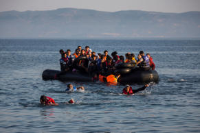 Migrants swim from an overcrowded dinghy with Syrian and Afghan refugees arriving from the Turkish coasts to the Greek island of Lesbos, July 27, 2015.