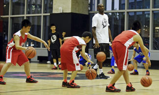 NBA basketball player Kobe Bryant of the Los Angeles Lakers looks on as young Chinese players play basketball during a promotional event in Shanghai, China, August 4, 2015. REUTERS/Stringer CHINA OUT. NO COMMERCIAL OR EDITORIAL SALES IN CHINA.