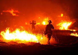 A firefighter lights a backfire as the Rocky Fire burns near Clearlake, Calif., on Monday, Aug. 3, 2015. The fire has charred more than 60,000 acres and destroyed at least 24 residences.