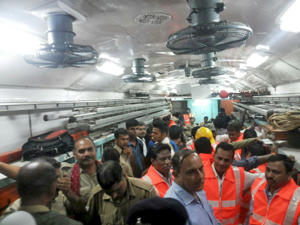 Officials and members of the rescue operation stand in a carriage of a derailed train near Harda, Madhya Pradesh in this handout provided by ANI on August 5, 2015. Two trains were derailed while they were crossing the Machak River, near Harda according local media.
