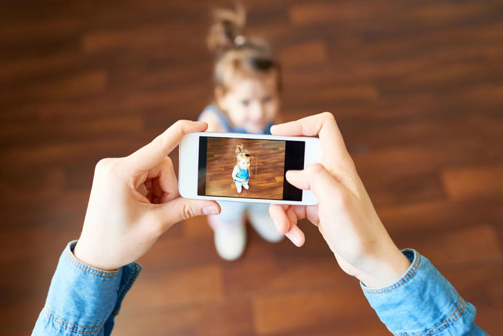 Parent taking a smartphone photo of a child