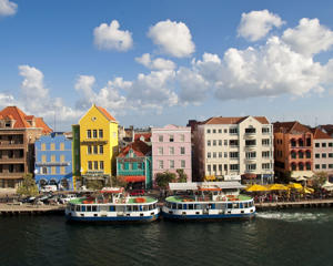 Pastel-colored colonial merchant houses line Handelskade, Punda waterfront, Willemstad, Curacao.