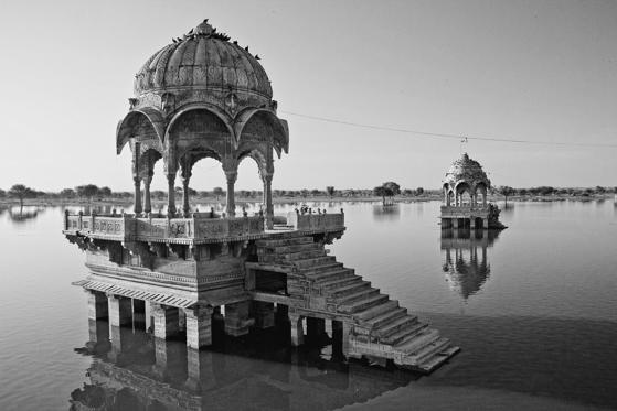 Artistically carved Chattris, temples, shrines and ghats surround banks of Gadisar Lake Jaisalmer,  Rajasthan, India.