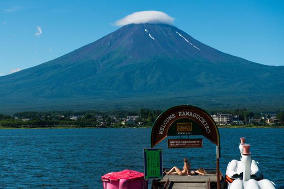 Tourists sunbathe on a pier on Lake Kawaguchiko as Mount Fuji stands behind the lake in Fujikawaguchiko, Yamanashi Prefecture, Japan.