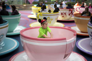 "A boy rides the ""Mad Tea Party"" during Disneyland's Diamond Celebration in Anaheim, California."