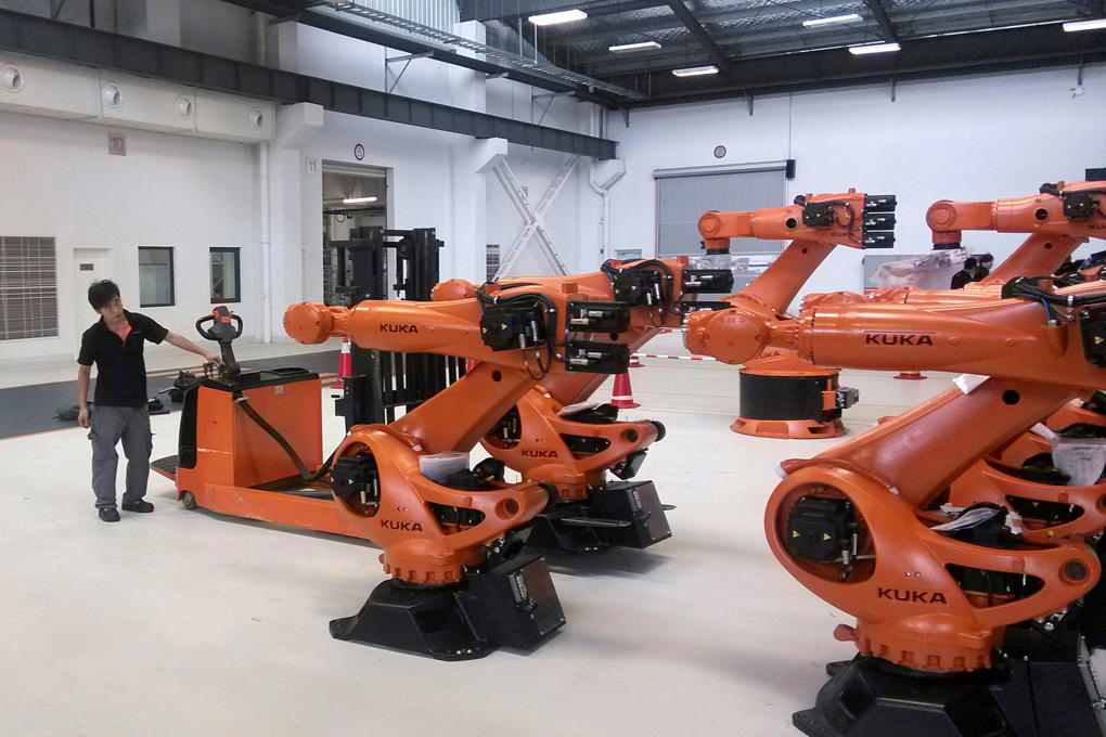 A staff member stands next to robots at a plant of Kuka Robotics in Shanghai August 13, 2014.