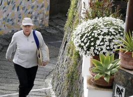 German Chancellor Angela Merkel enjoys a walk on the Ischia island, near Naples, Italy, on the way back from the thermal baths, in Sant'Angelo, Sunday, April 5, 2015. Angela Merkel and her husband are spending their Easter holidays on the Italian island of Ischia.