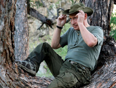 In this photo taken on Monday, Aug. 3, 2009, Russian Prime Minister Vladimir Putin adjusts his hat as he sits in a tree while traveling in the the Siberian Tyva region (also referred to as Tuva), Russia, during his short vacation.