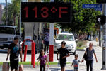 Pedestrians walk past a digital thermometer reading 113 degrees Fahrenheit in the Canoga Park section of Los Angeles. Richard Vogel/AP