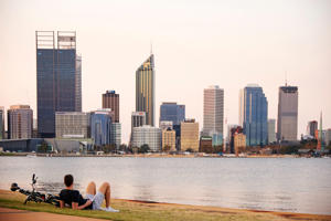 A man sits beside a bicycle along the bank of the Swan River in Perth, Australia.