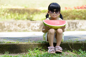 Little child with sunglasses and big slice of watermelon sitting in the park