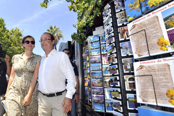 French President François Hollande (R) and his partner Valerie Trierweiler, pass by a postcards shop as they walk in the streets of Bormes-les-Mimosas, southeastern France, on August 3, 2012. François Hollande and Valerie Trierweiler spend their holidays at the Bregancon fort, one of the official Presidential residences since 1968.