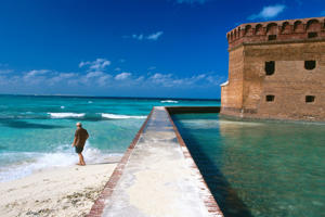 Tourist near moat wall of Fort Jefferson, Dry Tortugas National Park, Florida.