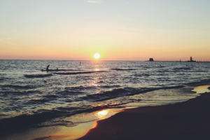 Swimmers enjoy Grand Haven beach at sunset in Michigan.