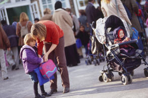 Woman bending over a child carrying a bag, another child in a pushchair behind.