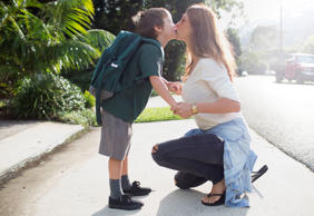 Mother kissing son outside school