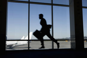 Man running to catch flight in airport.