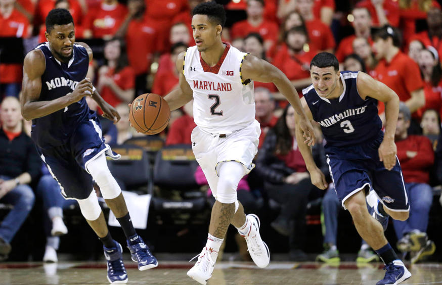 Maryland guard Melo Trimble, center, drives past Monmouth forward Brice Kofane, back left, and guard Max DiLeo in the second half of an NCAA college basketball game, Friday, Nov. 28, 2014, in College Park, Md.
