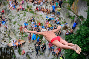 Italy's Pino Auber, 77, jumps from a 17-meter-high bridge over the Soca river in Kanal during a bridge diving competition on August 16, 2015.  AFP PHOTO / JURE MAKOVEC        (Photo credit should read Jure Makovec/AFP/Getty Images)