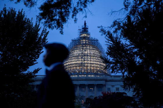 Domenique Malone walks past the U.S. Capitol building surrounded by scaffolding in Washington, D.C., U.S., on Wednesday, Oct. 28, 2015.