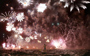 jan 1 A man rides a stand up paddle board as fireworks explode above him during ...