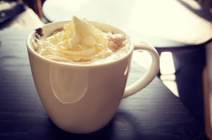 A yummy mocha coffee with delicious whipped cream, in a white mug on a dark wood table in a coffee shop.
