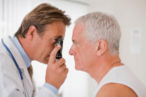 Doctor examining patient's eye in doctors office.