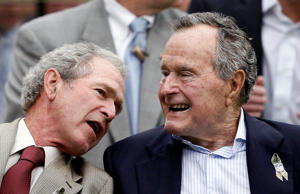 President George W. Bush, left, leans over to talk to his father President George H.W. Bush at Reliant Stadium in Houston, Texas.