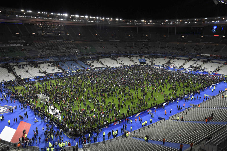 Spectators gather on the pitch of the Stade de France stadium following the friendly football match between France and Germany in Saint-Denis, after a series of gun attacks occurred across Paris as well as explosions outside the national stadium.