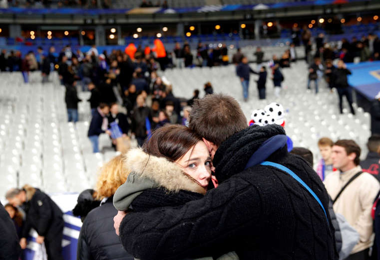 A supporter conforts a friend at the Stade de France stadium.