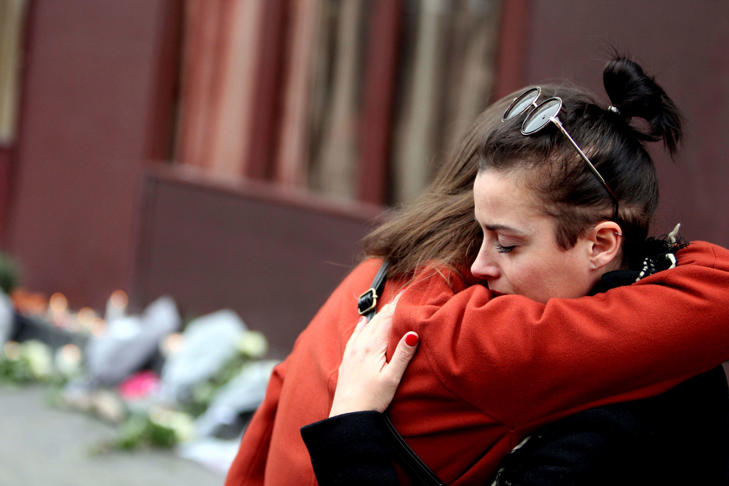 Two women embrace outside Le Carillon bar, Paris, one of the venues for the attacks in the French capital which are feared to have killed around 127 people.
