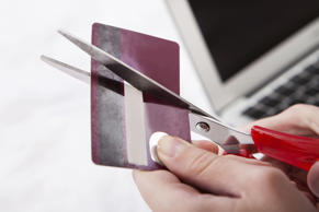 Close-up Of Hand Cutting Credit Card With Scissor
