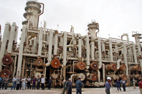 File: A picture made available on 22 March 2011 shows Iraqi workers near the second refinery unit for crude oil in Baiji refinery, Baiji, 180 km north of Baghdad, Iraq, on 21 March 2011.