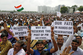 File: Members of the Patel community display placards as they attend a protest rally in Ahmedabad, India, August 25, 2015.