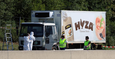 Police  walk near  a  truck that  stands on the shoulder of the highway A4 near Parndorf south of Vienna, Austria, Thursday, Aug 27, 2015.