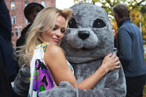 Actress Pamela Anderson poses with a person dressed as a seal as part of PETA's ...