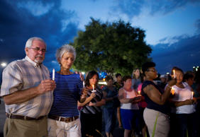 Buck and Carol Shepherd, of Roanoke, Va., along with others attending a candlelight vigil stand for a moment of silence for Alison Parker and Adam Ward, in front of the WDBJ-TV broadcast center Thursday, Aug. 27, 2015, in Roanoke.
